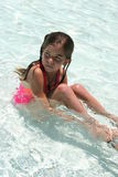 Lonely little girl in pool. Little girl sitting in the pool by herself stock images