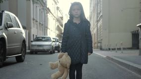 Lonely little girl posing in the street with her teddy bear, turning and go away stock video footage