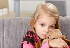 Lonely little girl sitting sadly on sofa Stock Photos