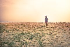 Lonely lost child toddler standing alone in sand dunes exploring childhood travel lifestyle stock photos