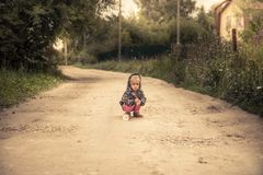 Lonely lost kid girl on rural road in countryside concept carefree childhood in countryside rustic lifestyle stock photo