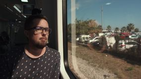 Handsome bearded man is sitting in a wagon of local train and looking in window stock video footage