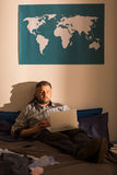 Lonely male using laptop. Photo of young lonely male using laptop on bed Royalty Free Stock Photography