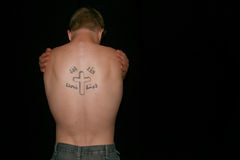 Lonely man. A topless man hugging himself, his back showing a crucifix tattoo Stock Photography