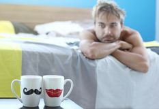 Lonely man in bed on pillow looks on two cups of morning tea or coffee, dreams about his missing girlfriend, weekend morning royalty free stock photography