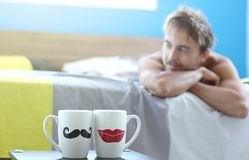 Lonely man in bed on pillow with two cups of morning tea or coffee, dreams about his missing girlfriend and smiles, weekend stock images