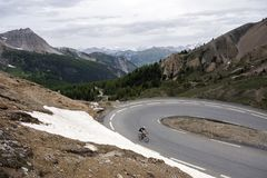 Lonely man on bicycle almost at the top of col d`izoard in the french haute provence. Lonely man on bicycle almost at the top of col d`izoard in the alps of stock images