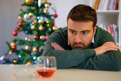 Lonely man celebrating christmas and drinking alone. Sad man in solitude drinking alcohol all alone during christmas Stock Image