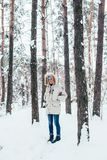 Young man in cold deep winter coat. Lonely man in cold winter jacket with furry hood, walks around and explores cold snowy forest or park Royalty Free Stock Photo