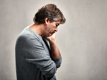 Lonely man. Depressed lonely man portrait over gray wall background Royalty Free Stock Photography