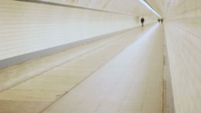 Lonely Man in Distance Walking in a Tunnel. Static medium long shallow depth of field shot of a distant unrecognizable middle aged man walking alone with his stock video