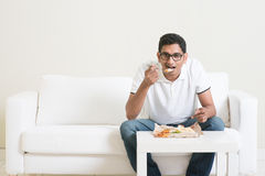 Lonely man eating food alone. Lonely young single Indian man eating food alone, copy space at side. Having nasi lemak as lunch. Lifestyle of Asian guy at home Stock Images