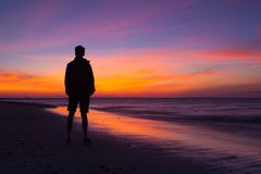 Lonely man on the empty beach at dramatic sunset. Cape Cod, USA. Cape Cod,Massachusetts, USA - July 13,2016: Lonely man on the empty beach at dramatic sunset stock images