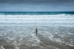 Lonely man entering the water at overcast beach Royalty Free Stock Photos