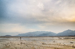 Lonely man far away on beach. In cloudy day sunset glow Royalty Free Stock Images