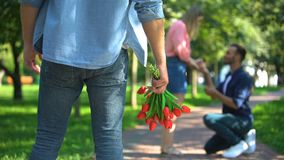 Lonely man with flowers watching male proposing marriage to his beloved girl. Stock footage stock video footage