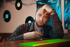 Lonely man gets drunk in a bar with glass of brandy Stock Photos