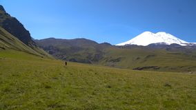 Lonely man is going to mount Elbrus by the slopes in Caucasus mountains. Pedestrian trekking stock video footage