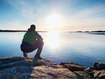 Lonely man hiker sits alone on coast and  enjoying sunset. View over rocky cliff to ocean. Lonely man hiker sits alone on the rocky  coast and  enjoying sunset Royalty Free Stock Photos