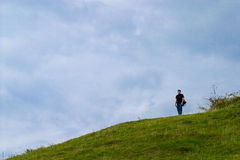Lonely man on hillside Royalty Free Stock Image