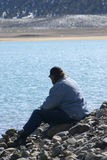 Lonely Man by the Lake. A lonely, solitary man sits fishing on the rocks next to the lakeshore. Pole is at his feet. Snow dusted mountains and blue lake Stock Photos