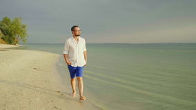 A lonely man in light clothes walks barefoot along the sand along the sea. Escape from cares, freedom and leave. 4K slow. A young, well-looking man in light stock video