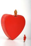 Lonely man miniature upon a red heart Royalty Free Stock Images