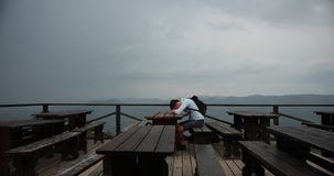 Lonely man in the mountains. Young handsome man lies his head on the arms sitting at the table with great view around. Him and rain falling over him stock video