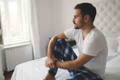 Lonely man in pajamas. Heartbroken lonely man in pajamas on bed stock photo