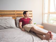 Lonely man playing his phone in his bedroom. Royalty Free Stock Image