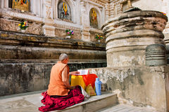 Lonely man read buddhist book on old Pali language. BODH GAYA, INDIA: Lonely man read buddhist book on old Pali language past a temple wall. BodhGaya is 1 of 4 royalty free stock images