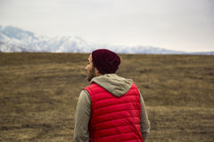 Lonely man in red waistcoat walking toward mountains background Stock Image