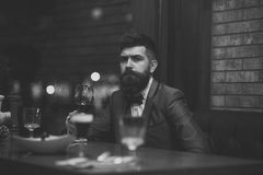 Lonely man in a restaurant. Date meeting of hipster awaiting in pub. Perfect wine. Businessman with long beard drink in. Cigar club stock photo