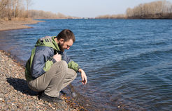 Lonely man on a river bank Royalty Free Stock Photos
