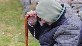 Lonely man with rosary and walking stick stock video