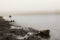 A lonely man in a rubber boat on the river early in the morning, closed by thick fog. stock image