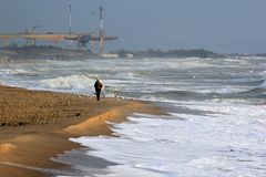 Lonely man on sandy beach at wintertime.  Royalty Free Stock Photos