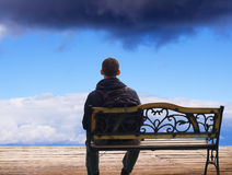 The lonely man sits on a decline. Creative Outdoor Photo Royalty Free Stock Photo