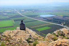 Lonely man sits on the edge of a cliff. And looks at the magnificent landscape of the Jezreel Valley, neighborhood Nazareth, Lower Galilee, Israel royalty free stock photography
