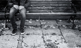 Lonely man sits on a wooden bench Stock Images