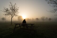 Lonely man silhouette sitting on a bench on a foggy morning