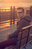 Lonely Man Sitting on a Bench during Sunset. Portrait of Young M Royalty Free Stock Images