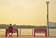 Lonely man sitting on a deck with another empty chair Royalty Free Stock Image