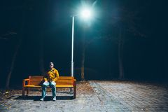 Lonely man sitting in night park. Under the light royalty free stock images