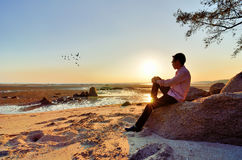 A lonely man sitting on the rock Royalty Free Stock Images