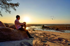 A lonely man sitting on the rock Stock Photo