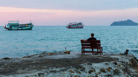 A lonely man sitting on the sea pier at dusk. Royalty Free Stock Image