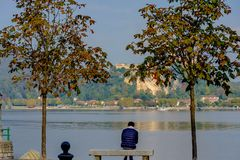 Lonely man sitting between two trees on a bench and looking at the lake. In the distance you can see the island on which stands th Royalty Free Stock Image