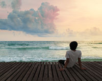 Lonely Man sitting in wooden dock pier in sea beach with twilight sky in sunset time and think concentrate Stock Images