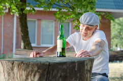 Lonely man smiling at his bottle of alcohol Stock Photography